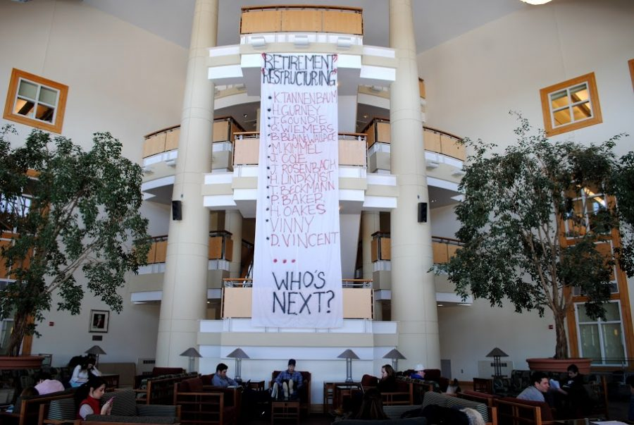 A banner protesting the recent changes in staff and administration hangs inside the Perry Atrium in Pettingill Hall