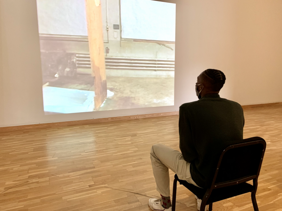 "Osceola Heard '22 watches ""The Way Things Go"" by Swiss artist duo Peter Fischli and David Weiss in the Bates Museum of Art"