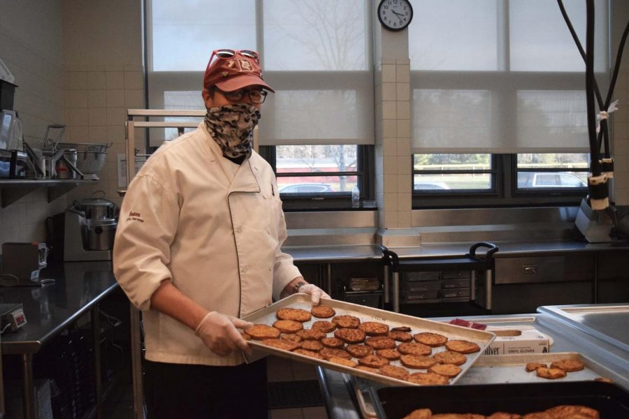 """Keith Pray holds a tray of breaded and fried eggplant slices. He said the dishes this year were simpler than usual and wished they could have been able to make the """"fancy stuff."""""""