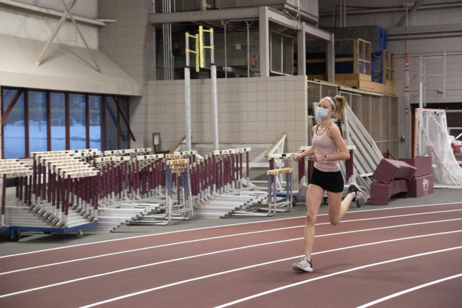 "Harper ""Maggie"" Marsh sprints a 200 m lap on the indoor track at the first indoor track and field practice on Tuesday. Women took turns running laps during this workout."