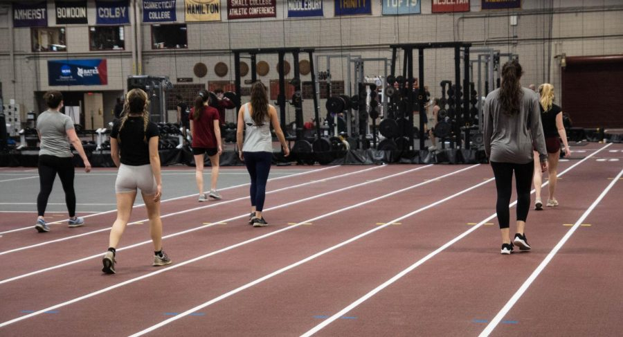 The women's track and field team warms up at their first practice on Tuesday. All athletes were required to wear masks for the duration of practice.